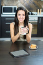 Kitchen woman using a tablet computer while drinking tea in her Royalty Free Stock Photos