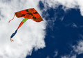 Kite sky clouds colorful mostly orange with white and dark blue as a background Stock Image