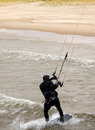 Kite surfer comes onto the beach this extreme sport found on icy winter waters of lake michigan guides his to land safely on Royalty Free Stock Images