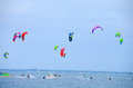 Kite surfing contest tampa bay florida surfer on in with many colorful kites flying through the sky Royalty Free Stock Image