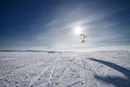 Kiteboarder with blue kite on the snow in covered freezing winter landscape crossed ski tracks Stock Photos