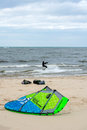 Kiteboarder and kite gear this extreme sport surfer plays happily in the icy winter water while another sports fan unfolds his Royalty Free Stock Images