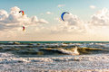 Kitesurfers ride kites through surfing waves of stormy sea at Blaga Beach resort at sunset Royalty Free Stock Photo