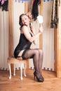 Kitsch retro boudoir girl checks her make up in black lingerie Royalty Free Stock Photography