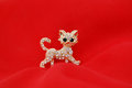 Kitty brooch with gem stones on red fabric background Stock Images