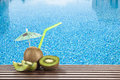 Kiwi fruit and cocktail with green drinking straw by the swimming pool Royalty Free Stock Photo