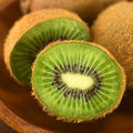 Kiwi fruit fruits on wooden plate selective focus focus on the half Royalty Free Stock Images