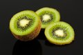Kiwi fruit slices on black background a high detail shot of with reflection a Royalty Free Stock Photo