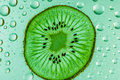 Kiwi fruit slices with water drops as background Stock Photos