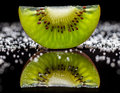 Kiwi fruit and sugar half a with reflected in a dark sheet lit from behind Stock Photo