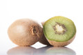 Kiwi fruit on a white background reflected in the table whole and sliced fruit Royalty Free Stock Photos