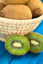 Kiwi fruits half on blue wood with in basket behind selective focus focus on the first half Royalty Free Stock Images
