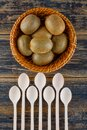 Kiwi fruits with spoons in a wicker basket on wooden background, top view Royalty Free Stock Photo