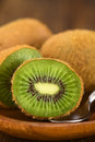 Kiwi fruits on wooden plate with spoon selective focus focus on the half Royalty Free Stock Image