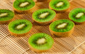 Kiwi slices on a bamboo mat, shallow focus Royalty Free Stock Images