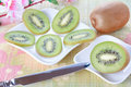 Kiwi slices on white plates and knife Royalty Free Stock Photos