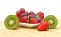 Kiwi, strawberries and grapes on a white background Stock Image