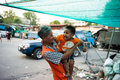 Klongtoey slum male meat market worker playing with his kid at in bangkok thailand Royalty Free Stock Photo