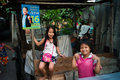 Klongtoey slum young girls under the electoral campaign sign of bangkok governor sukhumbhand paribatra at in bangkok thailand Stock Photo