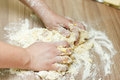 Kneading dough on the kitchen table closeup of woman hands Stock Image