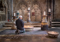 Kneel kneeling in prayer before a lit candle at lincoln cathedral england Stock Image