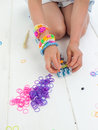 Kneeling childs hands making a multicoloured elastic band bracel braclet with colourful loom bands on loom against white table top Royalty Free Stock Photo