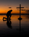 Kneeling before the cross with a man kneel in prayer on a beach at sunset Stock Photos