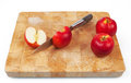 Knife cutting an apple on chopping board with two whole apples the side Stock Photos