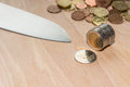 Knife cutting euro coins a cut a role of with pile of in the background Royalty Free Stock Photography