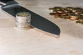 Knife cutting euro coins a through a role of with pile of in the background Stock Image