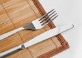 Knife and fork on bamboo tablecloth Royalty Free Stock Photography