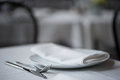 Knife, fork, plate and folded napkin upon white table cloth. Royalty Free Stock Photo