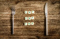 Knife and fork set on wooden table, sign saying Eat Royalty Free Stock Photo