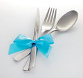 Knife fork and spoon with blue ribbon on a white background Stock Image