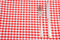 Knife and fork on tablecloth Stock Images