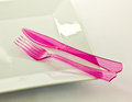 Knife and fork a white plate with a pink plastic Stock Image