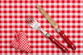 Knife and fort with red checkered heart and bow on table cloth Stock Photos