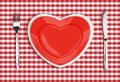 Knife heart plate and fork on red tablecloth checked Royalty Free Stock Photos