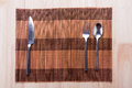 knife, spoon and fork with napkin on wooden table. Royalty Free Stock Photo