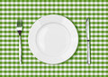 Knife white plate and fork on green picnic table cloth tablecloth Stock Photos
