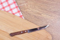 Knife on the wooden table with checkered tablecloth kitchen Stock Image