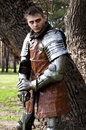 Knight with the sword near the tree in armor standing at and thinking Royalty Free Stock Photos