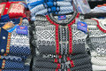Knit woolen sweaters norway black blue red and white in a pile for sale in a local outdoor market are popular souvenirs for Stock Image