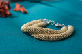 Knitted bracelet of gold color on a textile background close up Royalty Free Stock Image