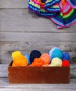 Knitted colorful striped mats and balls of bright woolen yarn in a wooden box on old wood wall background Royalty Free Stock Photo