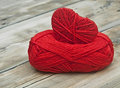Knitted heart and red of yarn on wood background Royalty Free Stock Photo