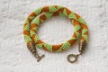 Knitted necklace from beads of light green and orange color close up Royalty Free Stock Photos