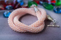 Knitted necklace from beads of pink color close up Stock Images
