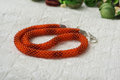 Knitted necklace from bright orange beads close up Royalty Free Stock Photos