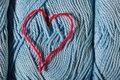 Knitted red heart on blue balls of yarn Royalty Free Stock Photos